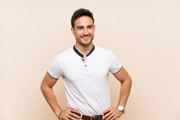 Handsome young man over isolated background posing with arms at hip and smiling