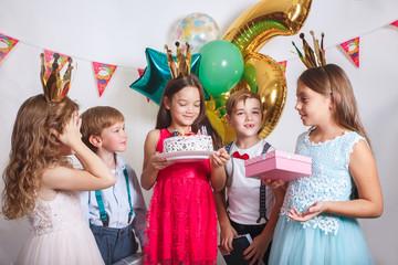 Children blowing birthday candles. Children birthday party