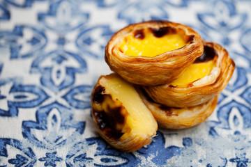Egg tart, traditional Portuguese dessert, pastel de nata. Blue background. Close up.