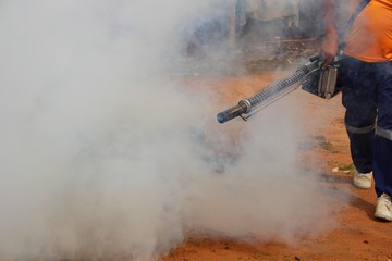 Employees are using fogging machines to get rid of mosquitoes to prevent dengue fever, take blurred pictures