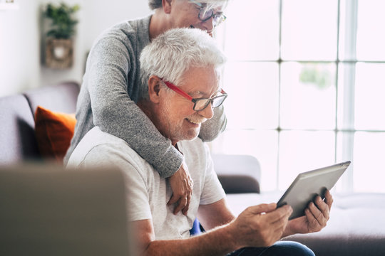 couple of seniors smiling and looking at the tablet - woman hogging at man with love on the sofa - indoor