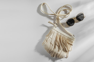 Wall Mural - Small white bag with fringe and sunglass. Summer Vacation concept.