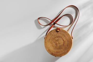 Wall Mural - Fashion round bamboo bag. Flat lay, top view. Spring/summer fashion concept.