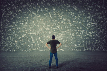 Rear view of puzzled student, hands on hips, stands in front of a huge blackboard try to solve hard...