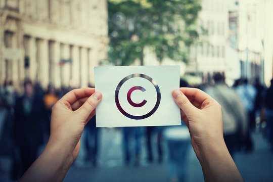 Hands hold paper with copyright symbol. International legal rights intellectual property sign, patent protection. Copyleft trademark license. Creation ownership against piracy crime