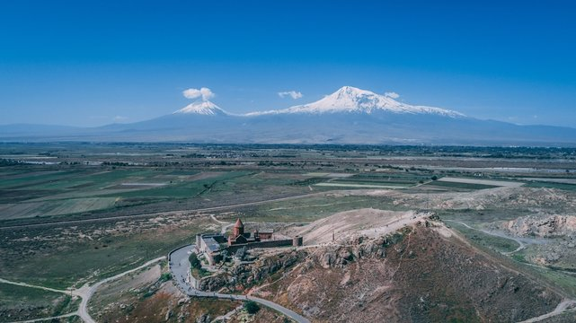 Aerial shot of an Armenian church on a hill with mountain Ararat and clear blue sky
