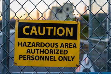 Caution sign for hazardous area on metal fence