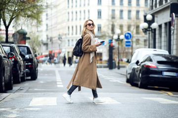 Pretty young woman crossing the street while holding the smartphone and looking sideways.