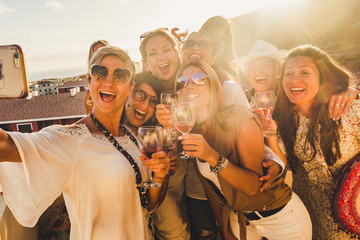 Happiness concept for caucasian young women friends laugh and have fun together in friendship taking a selfie picture with a smartphone - sun in backlight and view
