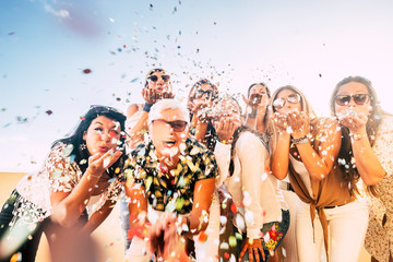 Confetti party celebration for happy cheerful crazy caucasian people women blowing out enjoying the event outdoor - carnival or birthday concept for cheerful pretty ladies