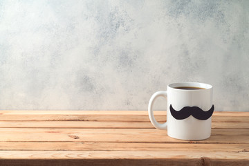 Happy Father's day concept with coffee mug and mustache over wooden background