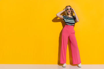 Happy Stylish Woman In Sunglasses, Pink Wide Legs Trousers, Sneakers And Striped Blouse Is Shouting Wall mural