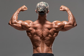 Rear view muscular man showing back muscles and biceps, isolated on the gray background. Strong male naked torso, workout Wall mural