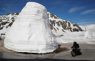 Walls of snow are seen beside as people ride on a bike during sunny weather on the St. Gotthard mountainpass road,