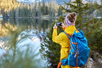 Freedom traveler takes pictures of scenic nature view, tries to capture beautiful lake with mountains and forest, stands back, carries big rucksack, explores hiking tours. People, recreation concept.