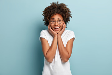 Optimistic carefree Afro female touches both cheeks, has broad smile, shows white teeth, dressed in casual outfit, round spectacles, stands against blue background, grins at camera, enjoys life