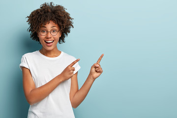 Happy smiling woman seller points at upper right corner, advertises item on blank space, has friendly facial expression, wears casual white t shirt, isolated on blue background. Look there, its nice