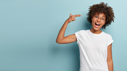 Glad dark skinned curly woman shoots in temple, tilts head, keeps mouth widely opened, dressed in casual white t shirt, demonstrates suicide gesture, isolated on blue background with blank space