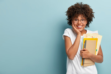 Pleasant looking Afro American woman holds notepads, papers, studies at college, glad to finish studying, keeps hand on cheek, wears white t shirt, isolated on blue background with blank space