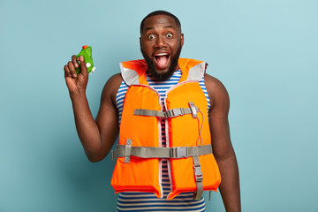 Overjoyed dark skinned man has water fighting with friends at beach, exclaims happily, wears orange lifejacket, has fun, plays on seaside with squirt gun, isolated on blue background. Real battle