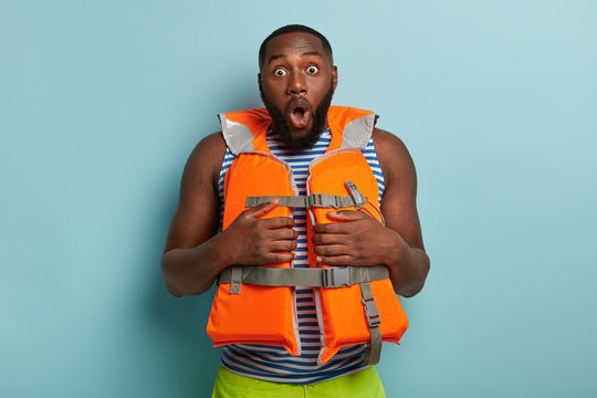 Stupefied dark skinned man dressed in life jacket, shocked to have emergency situation, has thick beard, bugged eyes, isolated on blue background, prepares for ride on banana. Water activities
