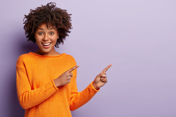 Photo of delighted African American woman points away with both index fingers, promots awesome place for your advertising content, isolated over purple background, gives advice, shows copy space Wall mural