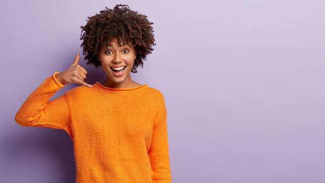 Delighted young female model with happy expression, makes call gesture, asks being in touch, wears casual orange jumper, isolated over purple background with free space for your advertisement
