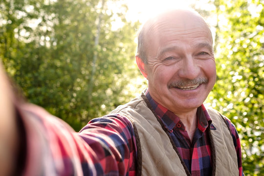 Selfie from handsome senior hispanic man on sunny day. Cheerful senior man making a photo on vacation