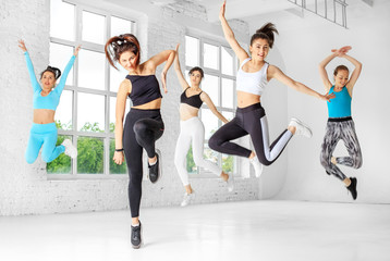A group of girls jumping to dance in the dance class. The concept of sports, a healthy lifestyle, fitness, stretching and dancing