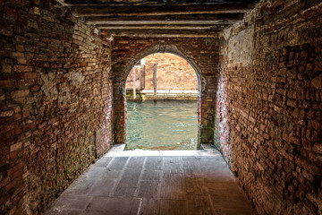 Fototapete - Exit to the water canal from courtyard, Venice, Italy. Vintage corridor of yard of residential houses. Ancient architecture of Venice. Old street of the Venice city. Antique pedestrian brick tunnel.