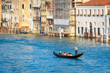 Fototapete - Gondola with tourists sails on the Grand Canal, Venice, Italy. Water trip on a gondola in summer Venice. Panorama of the Venice city with lone boat. Romantic travel across old Venice.