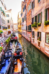 Fototapete - Street with moored gondolas and cafe, Venice, Italy. Scenic view of the Venice canal in summer. Colorful vintage houses of Venice with flowers. Romantic tourist water trip in the old Venice city.