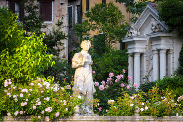 Fototapete - Scenic view of a street in Venice, Italy. Old houses with beautiful garden on Grand Canal in the Venice center. Classic marble statue in flower garden in summer. Nature and architecture of Venice.