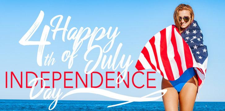 Beautiful cheerful woman holding an American flag on the beach.