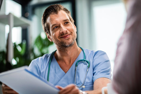 Smiling male doctor talking to his patient while going through medical reports at his office.
