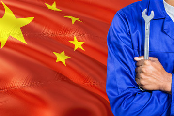 Chinese Mechanic in blue uniform is holding wrench against waving China flag background. Crossed arms technician.