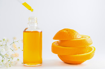 Vitamin C serum in cosmetic bottle with dropper, sliced orange and flowers on white background. Organic SPA cosmetics with herbal ingredients.