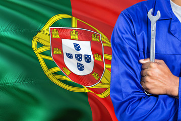 Portuguese Mechanic in blue uniform is holding wrench against waving Portugal flag background. Crossed arms technician.