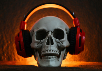 Skull music with headphone / Human skull listening to music earphone decorated at halloween party