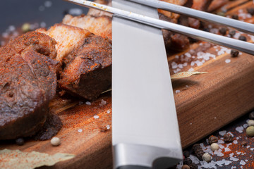 Close up of Carving Fork and Knife with Oven Roasted Pork on wooden cutting board. Wall mural