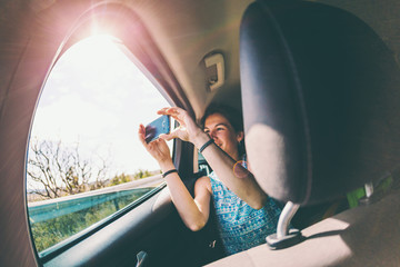 A girl sits in the back seat of a car and takes a photo of a passing landscape from a window.