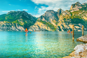 Wall Mural - Surfers in lake during surfing near Torbole, lake Garda, Italy