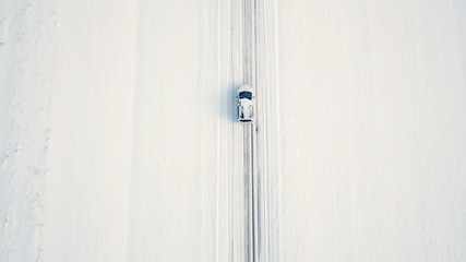 Top view of single car in middle of snow landscape