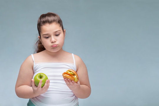 Portrait of a young beautiful girl holding a red Apple in one hand and a hamburger in the other on a white background .A true expression of positive emotions. the problem of childhood obesity