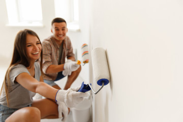 Happy Couple Painting a Wall with a Paint Roller. Selective focus on roller