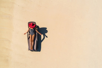 Aerial view of slim woman sunbathing lying on a beach chairin Seychelles. Summer seascape with girl, beautiful waves, colorful water. Top view from drone.