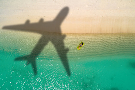 Concept of airplane travel to exotic destination with shadow of commercial airplane flying above beautiful tropical beach. Beach holidays and travel.
