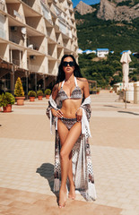 sensual woman with dark hair in luxurious swimming suit and accessories posing near open air swimming pool