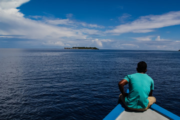 Man sitting on a traditional wooden boat heading over the calm tropical ocean towards a luxury resort on the atoll of the Maldives