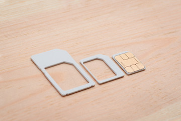 Nano sim card and adapters for different size on wooden table. Choosing right size of a SIM card for mobile phone